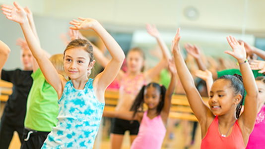 Kids waving their arms in a dance class