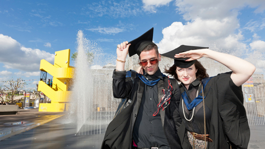 Two graduates in front of a waterfall