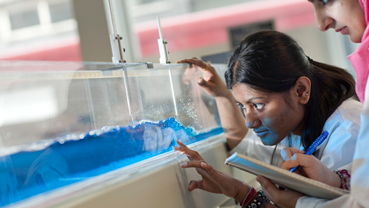 A student looking at blue liquid in a lab