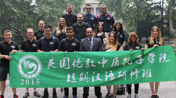 Students in China standing in front of a big green flag with Chinese script on