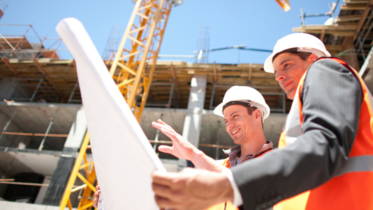 Construction workers study plans on-site