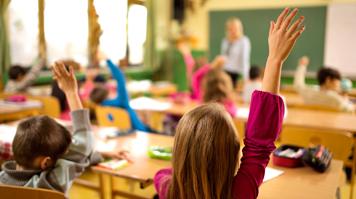Girl raises hand in classroom