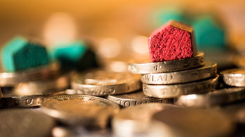 Mini-houses photographed on a stack of coins