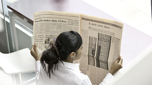 Students read newspapers to research and analyse economics