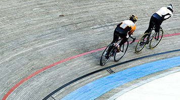Two cyclists riding in a velodrome