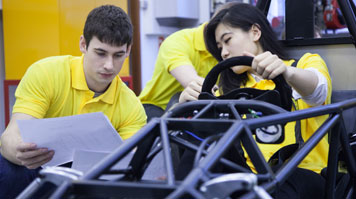 Engineering students working on the chassis of a formula one racing car