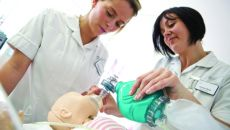 A nursing student is shown how to use equipment on a dummy patient