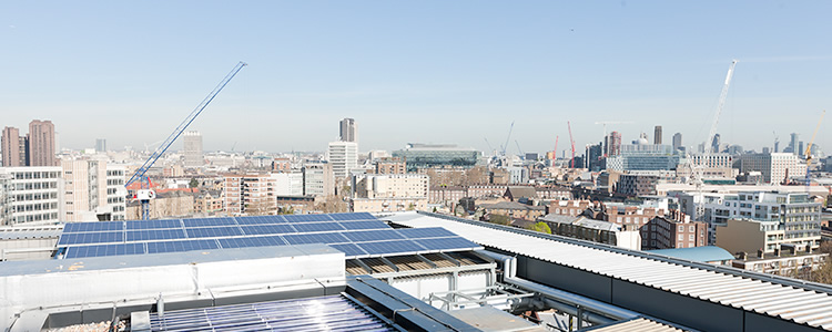 Rooftop view of London with solar panels in foreground