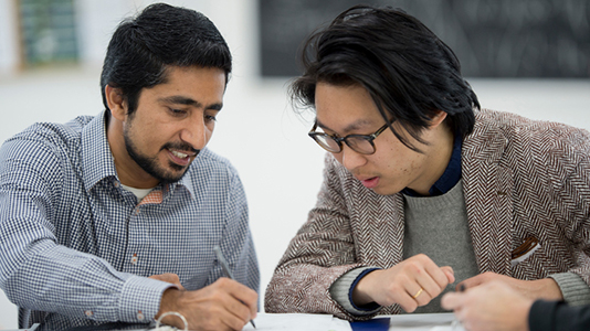 Two men writing on a piece of paper