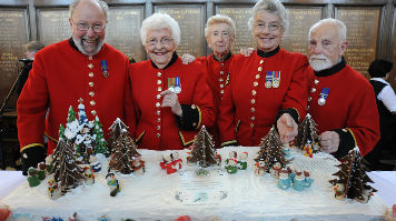 Chelsea Pensioners posing with the impressive cake
