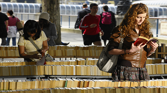 Students reading books at a market on Southbank