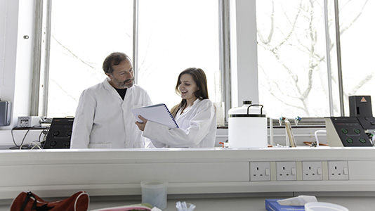 A student and lecturer in the microbiology lab