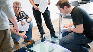 Students and staff looking at clear glass panels in the floor, with pipes and energy cells set in the floor.
