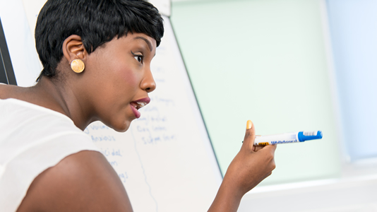 Female lecturer holding a pen