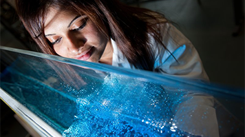 Female student in a white coat at a workbench examining blue liquid in a clear perpex container