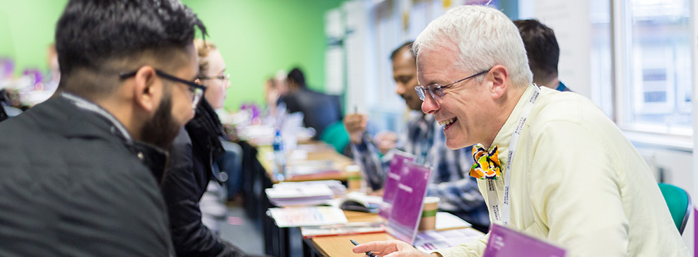 A lecturer laughing with a student at a London South Bank University (LSBU) Open Event
