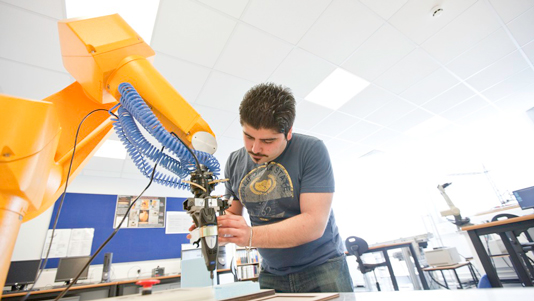 An engineering student using equipment in a lab