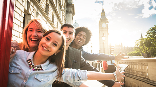 Four friends in London in front of Big Ben