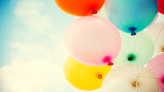 A bunch of colourful balloons against the sky