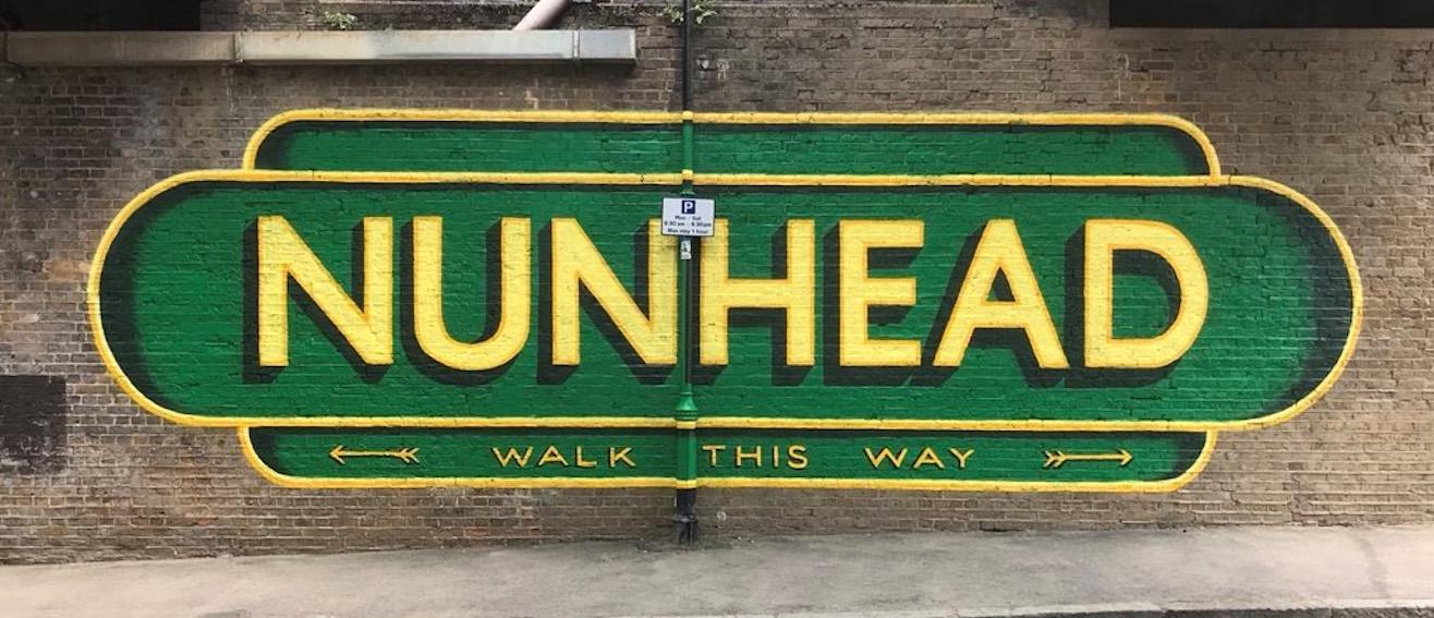 Yellow writing on wall saying Nunhead
