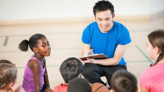 Sports coach talking to kids