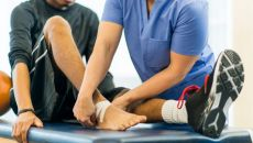 Man having foot taped during sports therapy session