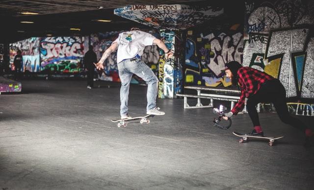 woman films man skateboarding