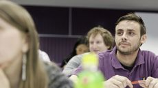 Man in a purple shirt at a lecture