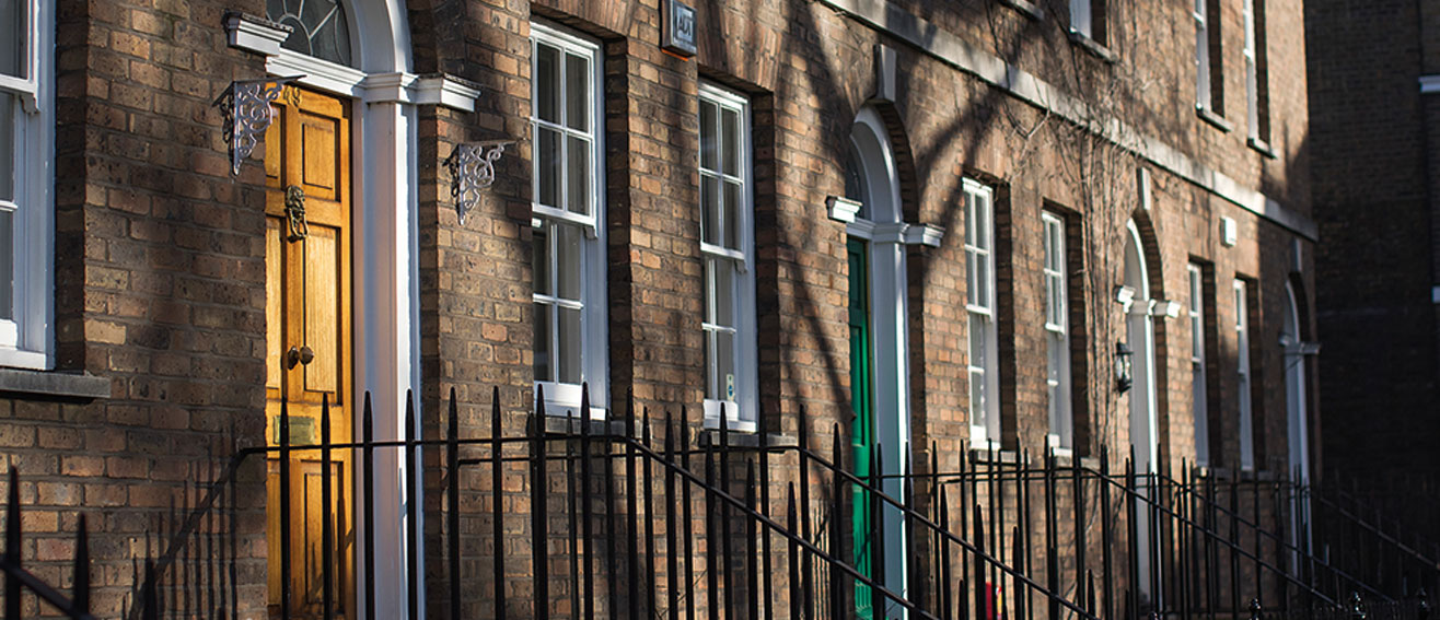 terraced houses with black railings and different coloured doors