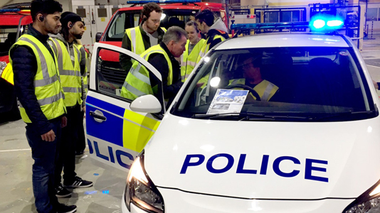 Students look at a police car
