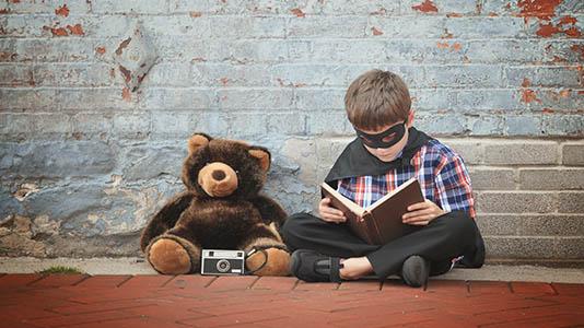A boy in a superhero mask reading a book next to a teddy bear