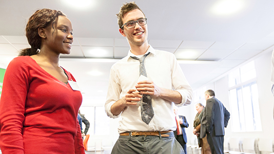 A man and a woman in conversation at a professional event