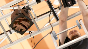 A student works on a lighting rig in a theatre