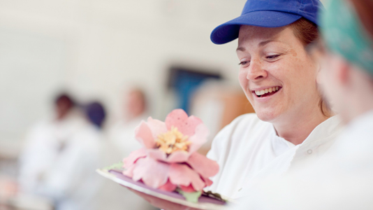 A baking student holding a flower shaped cake