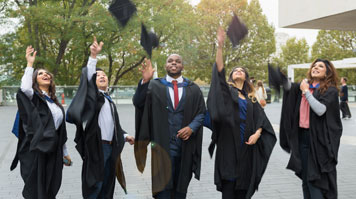 Graduates throw their mortarboards into the air outside the Royal Festival Hall